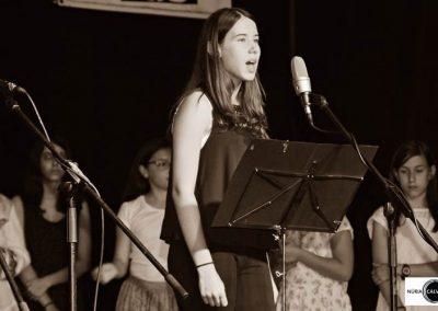 Noia cantant sobre escenari