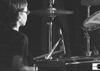 Niño tocando la batería en concierto