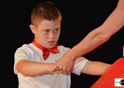 niño bailando de la mano con profesora sobre escenario