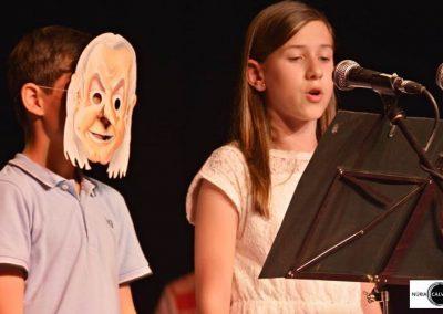 Niño con máscara y niña cantando en concierto