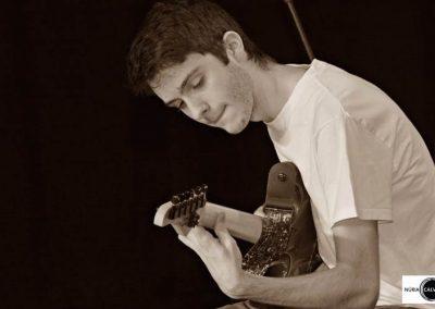 Joven tocando la guitarra en concierto
