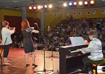 profesora y alumna tocando el violín y chico tocando el piano
