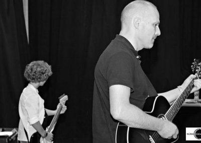 Profesor y alumno tocando la guitarra en concierto de música