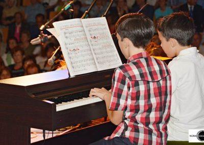 Dos niños tocando piano en concierto