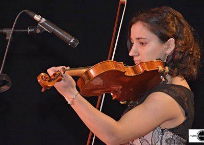 Chica tocando violín en concierto