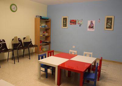 Aula infantil con mesas y bancos de diferentes colores