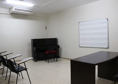 Aula de Classes amb pissarra, bancs i piano
