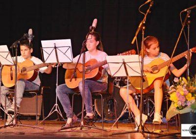 Niños tocando la guitarra sobre un escenario