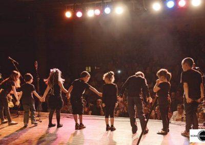 Niños saludando al público sobre un escenario