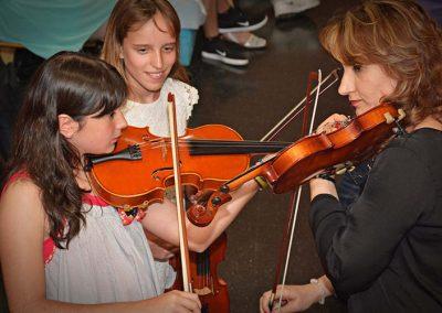 Niña y Profesora tocando el Violín. Otra niña las observa en segundo plano